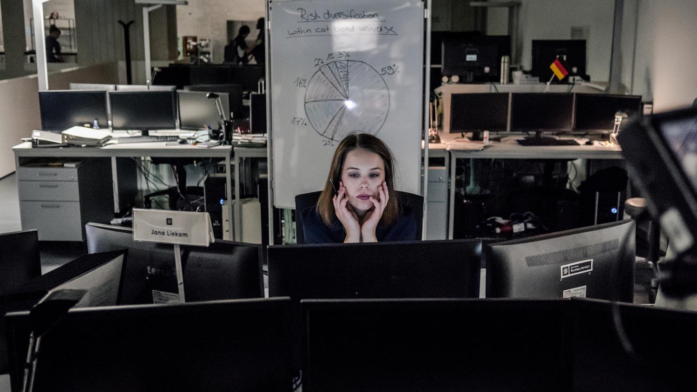 Jana Liekam (Paula Beer) sitzt an ihrem Schreibtisch hinter mehreren Bildschirmen und arbeitet. Es scheint spät zu sein, denn die anderen Arbeitsplätze im Großraumbüro sind leer.
