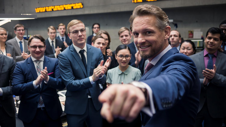 Gabriel Fenger (Barry Atsma) weist mit einer Handbewegung auf jemanden hin, der im Bild nicht zu sehen ist. Hinter ihm stehen seine Kollegen und klatschen Beifall.