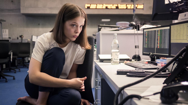 Merklich müde und überarbeitet sitzt Jana (Paula Beer) nachts im Büro und arbeitet. Die junge Frau hat ihre Schuhe ausgezogen, hockt mit angezogenen Beinen auf ihrem Bürostuhl und schaut nahezu apathisch auf die Monitore vor sich.