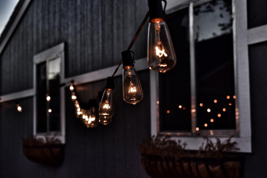 Eine Reihe großer Glühbirnen bildet eine Lichterkette, die sich von der Fassade eines grauen Holzhauses hin zur Kamera erstreckt und in der Dämmerung für Beleuchtung sorgt.