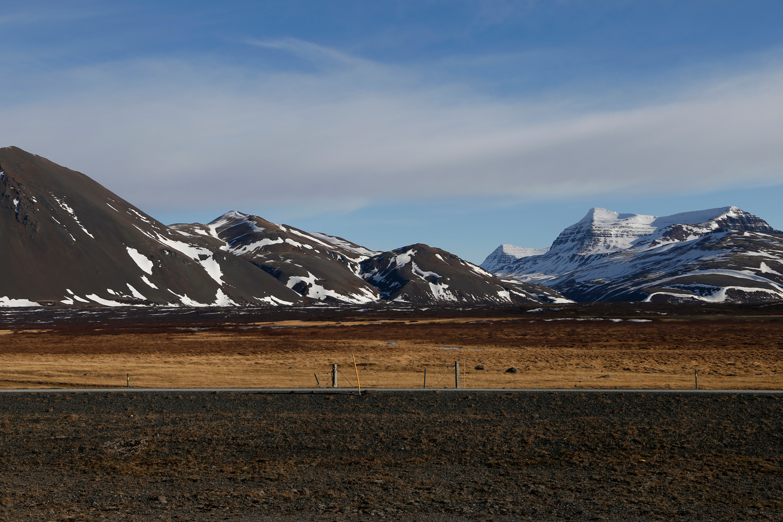 Eine verlassene Straße verlauft in einer geraden Linie horizontal am Fuße einer schneebedeckten Bergkette, die im Sonnenlicht glänzt.