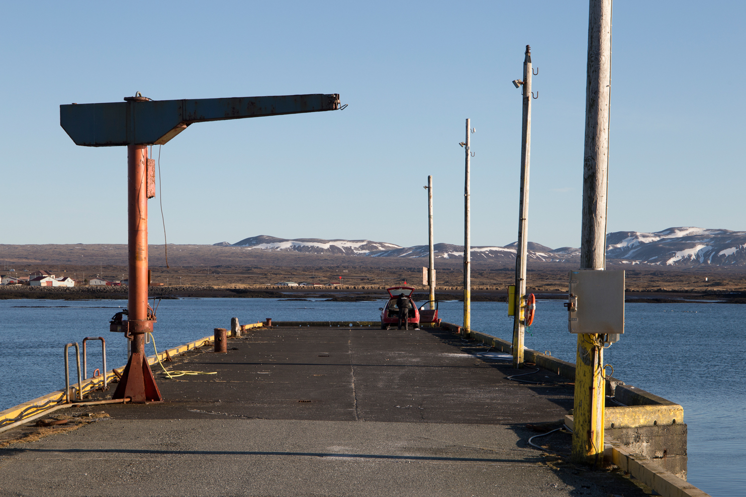A man has parked his tiny red car at the end of a pier and is unloading his fishing gear while the sun is shining on a deserted harbour framed by distant mountains.