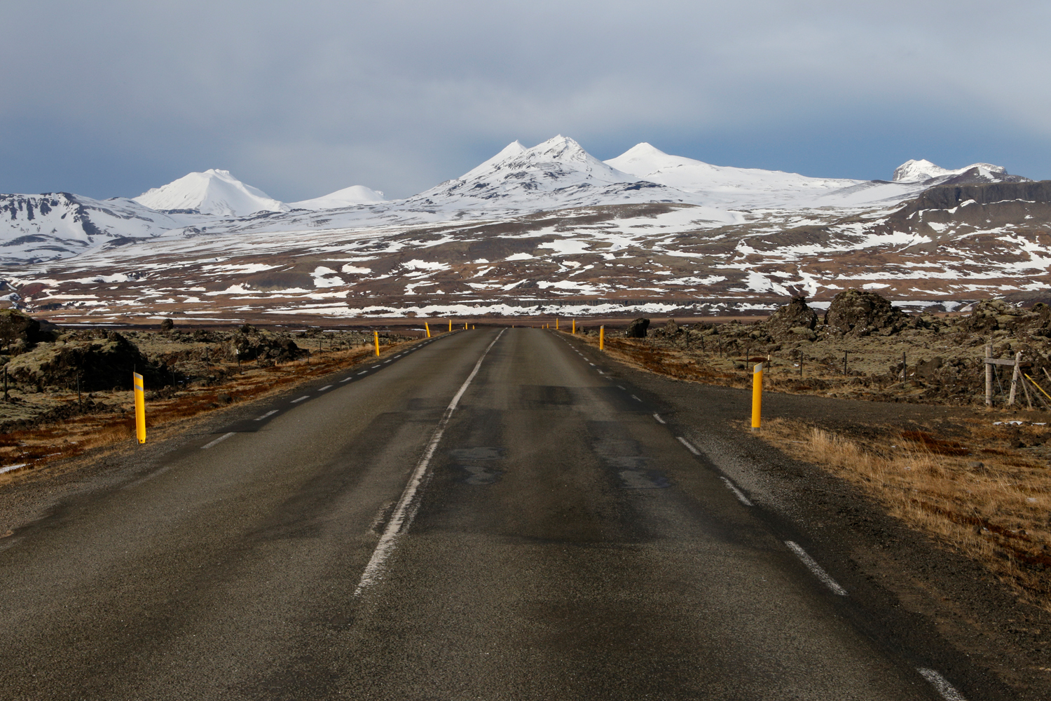 An empty street stretches from the foreground to the horizon in an almost straight line, leading through fields of volcanic rocks with distinctive green lichens growing on the surface towards a jagged mountain chain that is covered in snow.