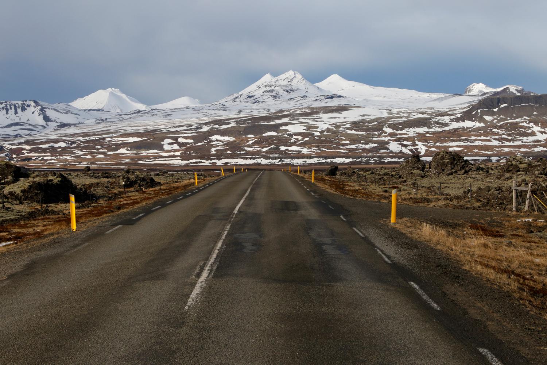 Eine verlassene Straße führt vom Bildvordergrund in einer beinahe geraden Linie zum Horizont, an Feldern voller vulkanischer Felsbrocken vorbei, die mit grünen Flechten überzogen sind, hin zu einer zackigen Bergkette, die von hohem Schnee bedeckt ist.
