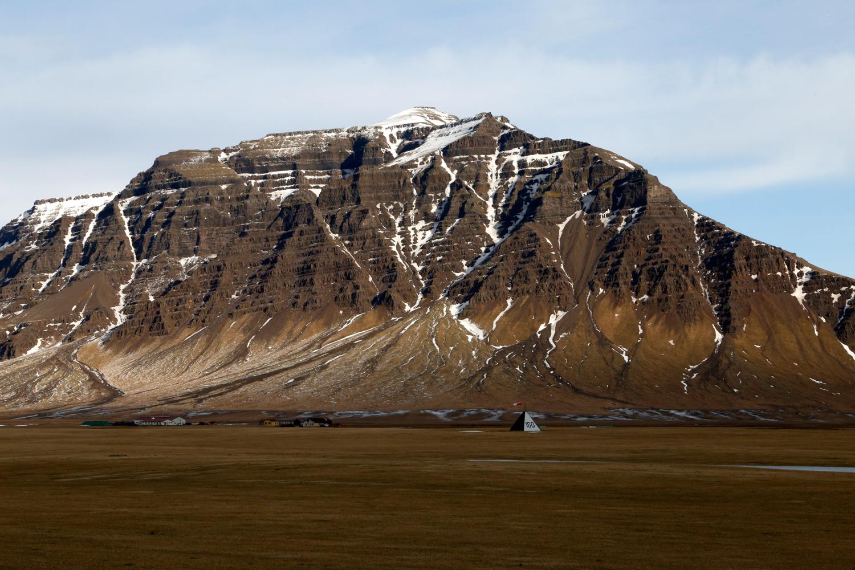 Am Fuße eines Berges, der aus Schichten von Vulkangestein geformt wurde, die sich in streng geometrischer Form aufeinandergetürmt haben, steht ein kleines, tetraedrisches Zelt, an dessen Spitze ein Windsack befestigt wurde.