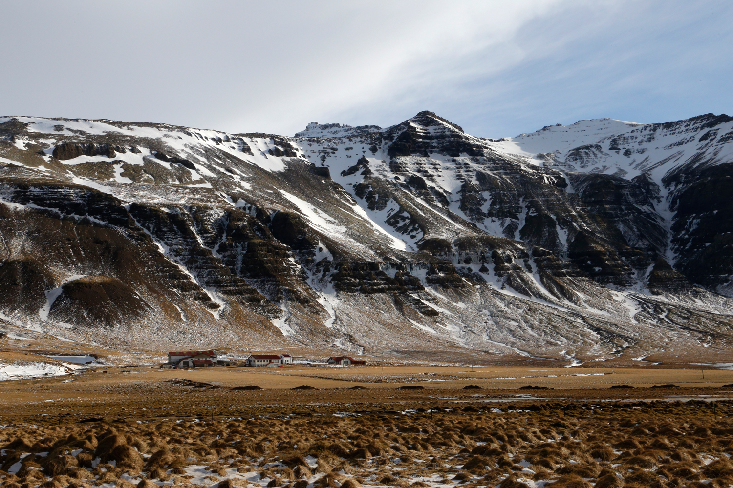 A farm at the bottom of a very steep mountain chain, sitting in a field of dry grass with some occasional spots of snow.