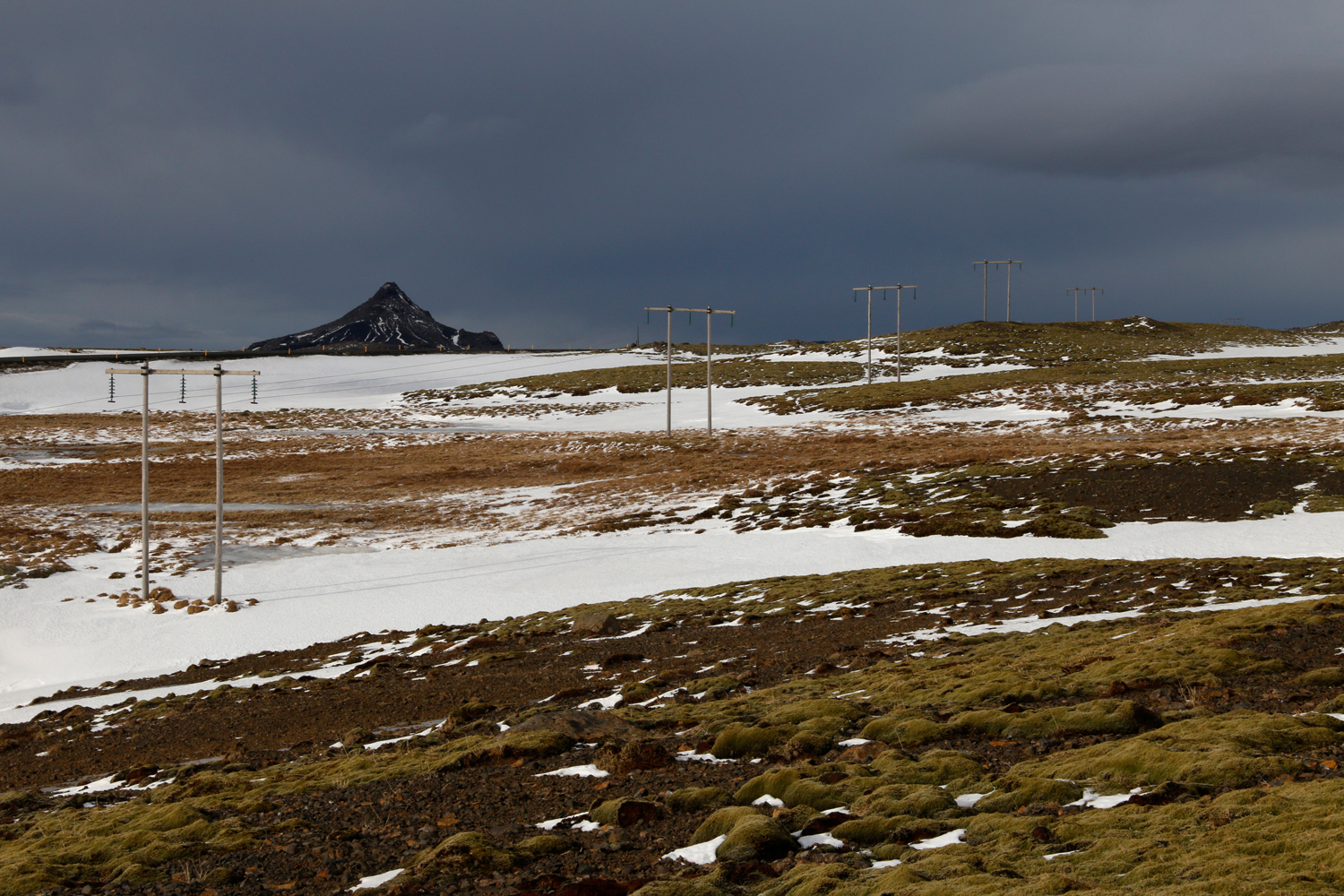 Transmission towers lead up a hill that is covered in the green of lichens, the white of unspoilt snow and the light brown of dry grass, with a black, jagged mountain in the distance and dark clouds looming above.