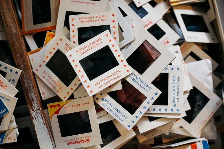 Dozens of Kodachrome film negatives are piled up in a wooden drawer, each of them protected by a white 'transparency' frame.