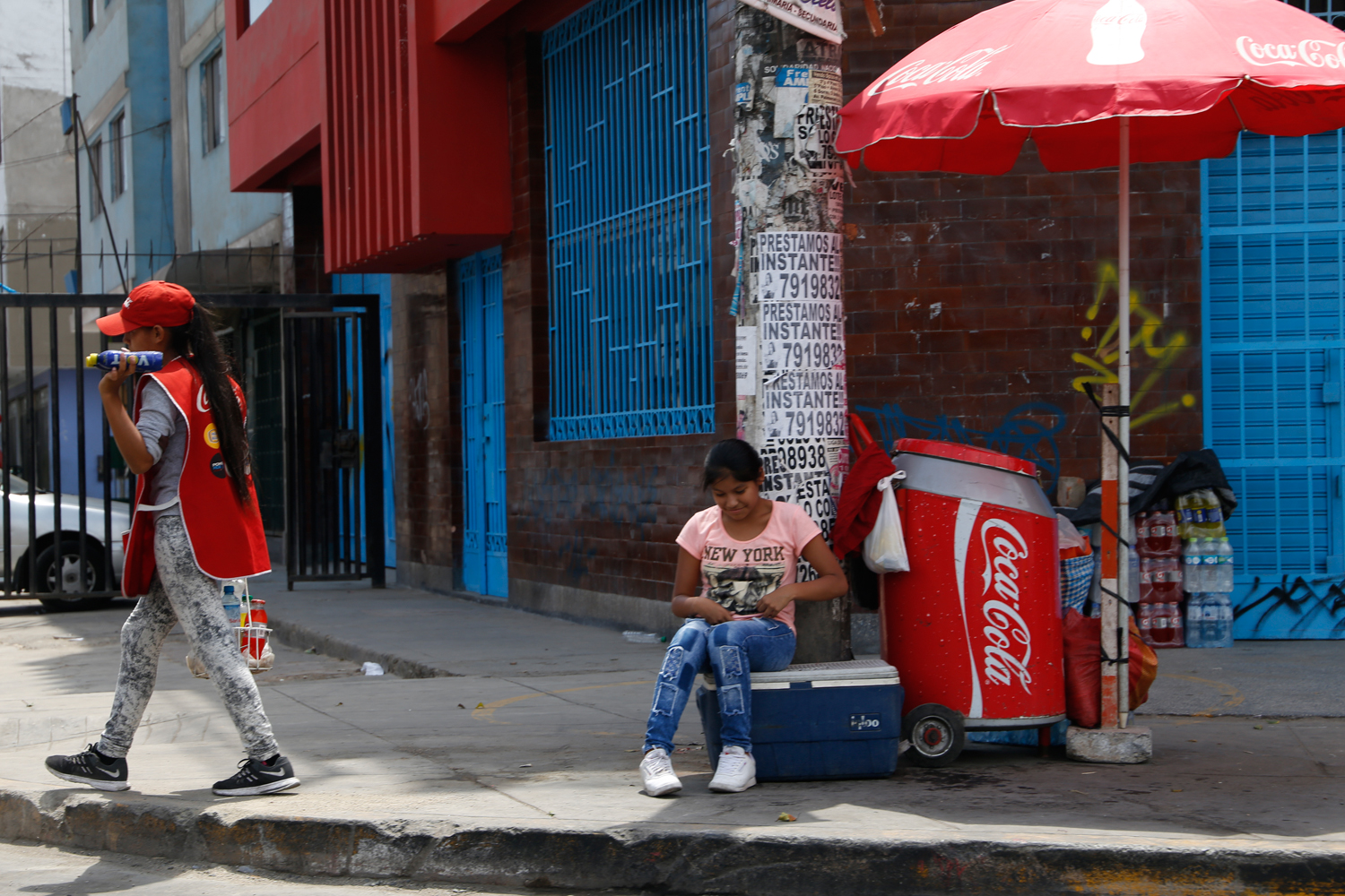 Two girls operate a mobile kiosk on the side of a road. One of them is sitting on a plastic box next to a stack of bottled lemonade, shaded by a red Coca Cola parasol. The other one is walking along the curb with a small crate of plastic bottles to be sold to people passing by in cars.