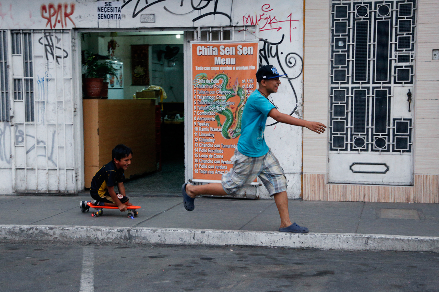 Two boys race along the pavement in front of a typical Chinese-Peruvian Chifa restaurant. The older one in his Crocs-style shoes is running from the younger one who is kneeling on a red plastic skateboard. Both are laughing heartily.