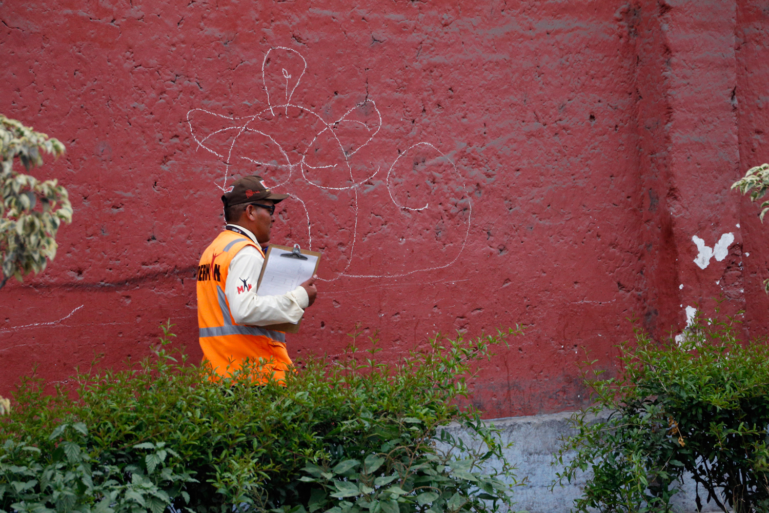 A public servant wearing an orange reflective vest and carrying a clipboard with a blank sheet is walking past a red wall that features a large, clumsy graffiti roughly resembling a face.