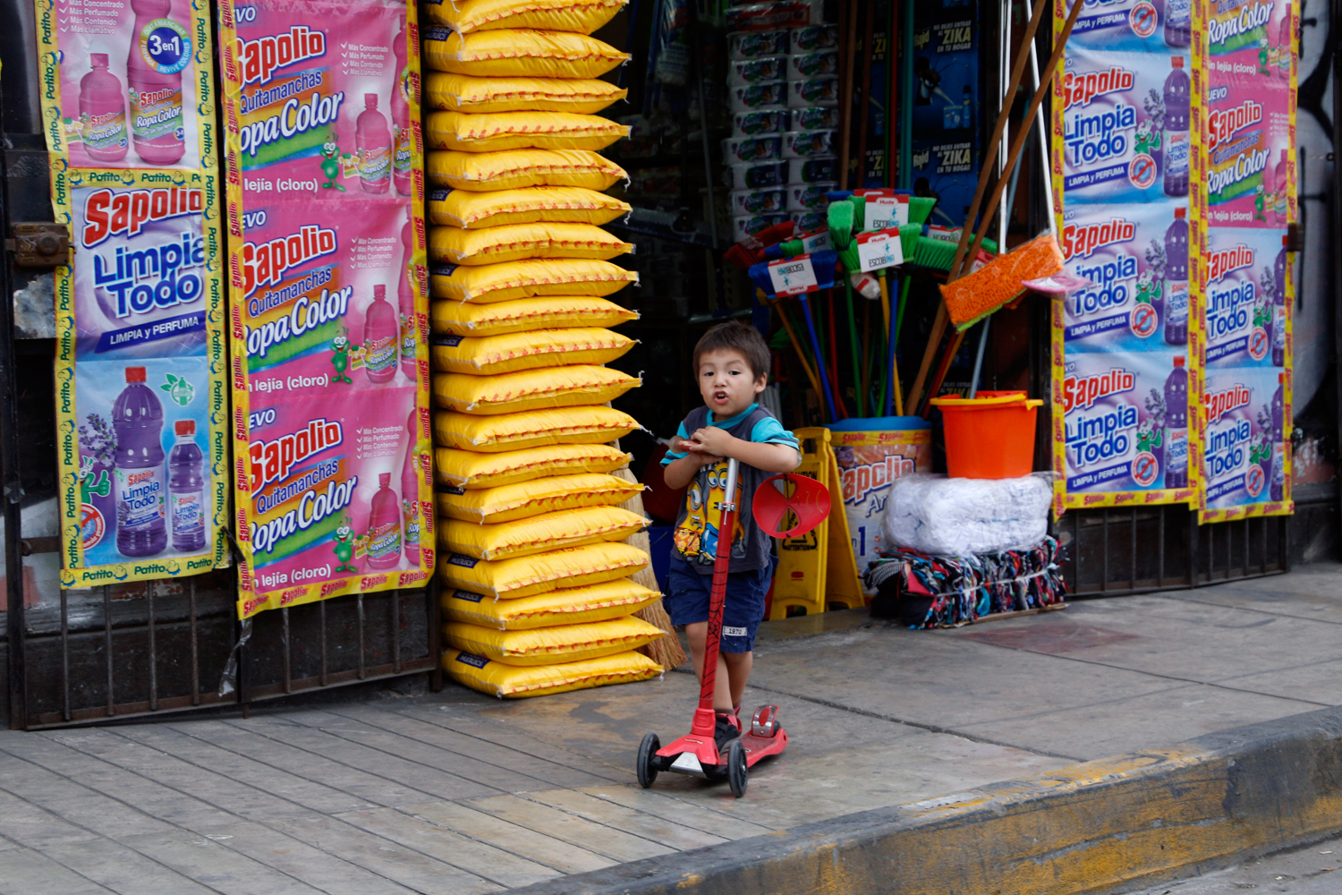 A young boy is riding his red scooter along the pavement in front of a shop that sells cleaning supplies. His shirt features two Minions from the Despicable Me movie franchise and a Spider Man mask is dangling from the handlebar of his scooter.