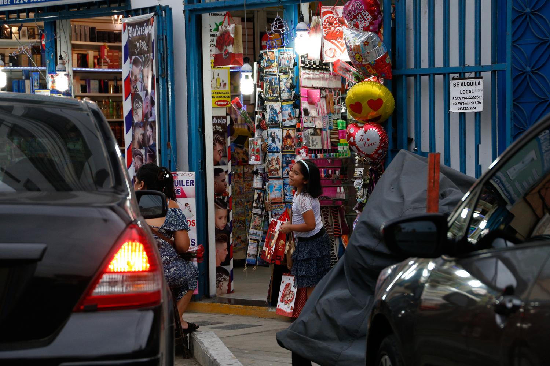 Ein scheinbares Paar von Mutter und kleiner Tochter arbeitet in einem kleinen Laden am Straßenrand, der Zeitschriften, Luftballons und Kosmetikprodukte verkauft. Das Mädchen beißt auf ihre Unterlippe und lächelt, vermutlich um die Aufmerksamkeit ihrer Mutter zu gewinnen.