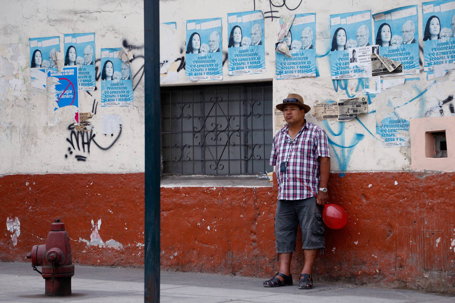 A sulky expression crosses a man's face as he leans against a wall, holding but almost dropping a red balloon. He is wearing a chequered shirt and a brimmed hat. The wall is covered in posters carrying various political messages. There are almost a dozen posters protesting the privatisation of Lima's water supply. A single poster, half torn off, objects to the alleged teaching of the 'gender ideology' in schools.