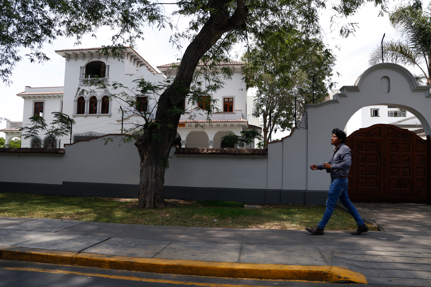 A young man wearing fitted jeans, shiny leather shoes and a dark grey shirt walks along the pavement in an upscale neighbourhood of Lima. He is passing the tall wooden gate to a three-storey, colonial-style villa, painted all white and shaded by a number of trees in its extensive, enclosed garden.