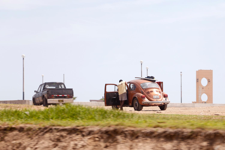 Ein junger Mann lehnt sich in die offene Tür eines bronzefarbenen VW-Käfers, der in der Nähe des Strands geparkt ist. Ein Surfbrett und ein Neoprenanzug liegen auf dem Dach, über der geöffneten Tür auf der Beifahrer*innenseite hängt ein Handtuch.