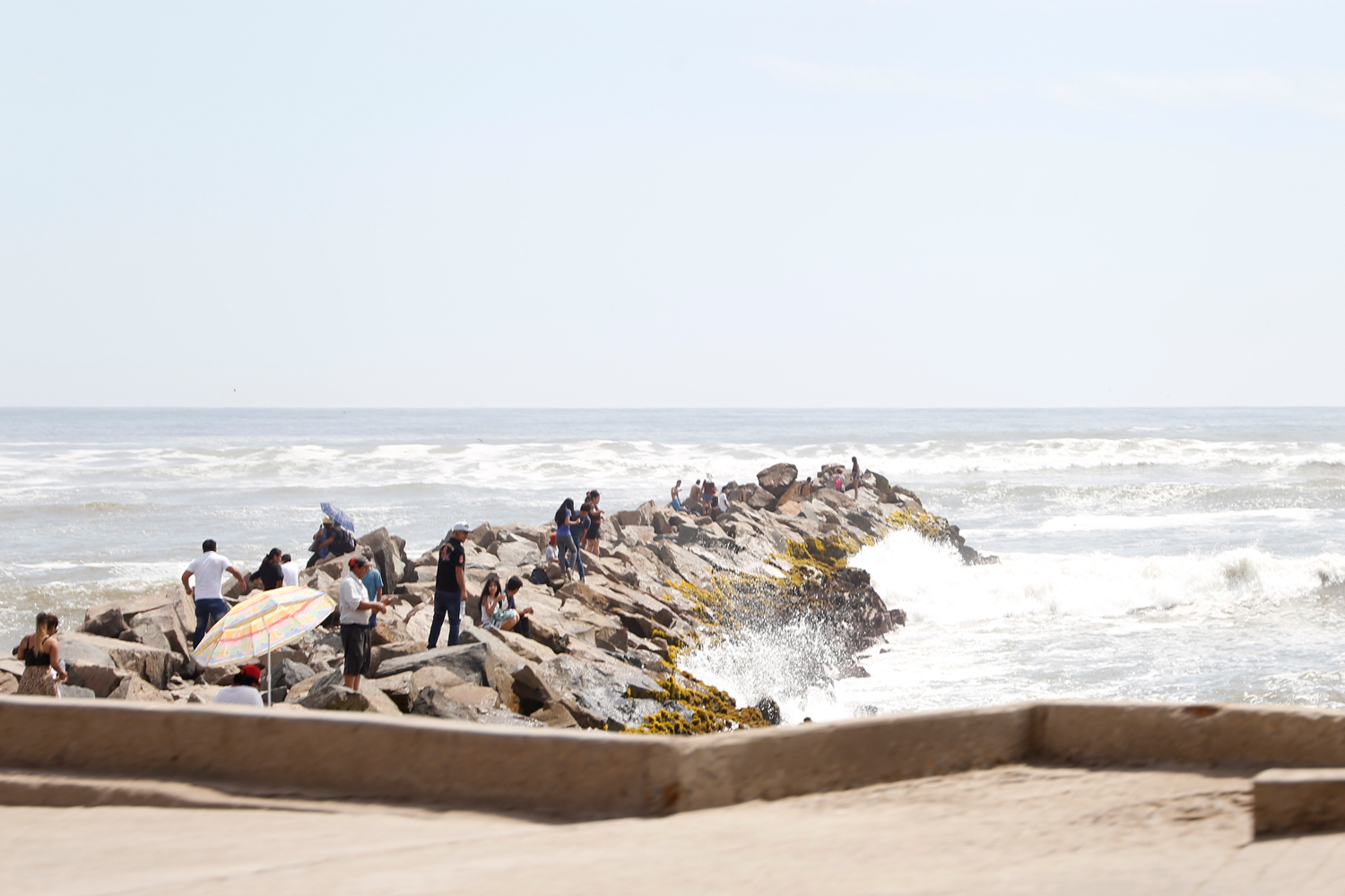 About two dozen people have come to a rocky pier that stretches from the beach promenade into the sea. Some are sitting on the rocks, others are standing around in small groups as high waves crash onto the edge of the pier.