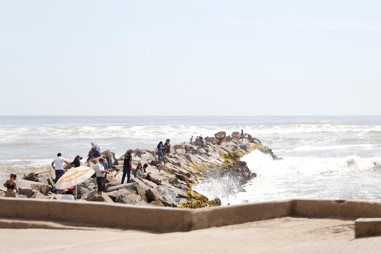 Rund zwei Dutzend Leute sind zu einem felsigen Pier gekommen, der sich von der Strandpromenade ins Meer erstreckt. Manche sitzen auf den Felsen, andere stehen in Grüppchen zusammen, während sich am Rande des Piers die hohen Wellen brechen.
