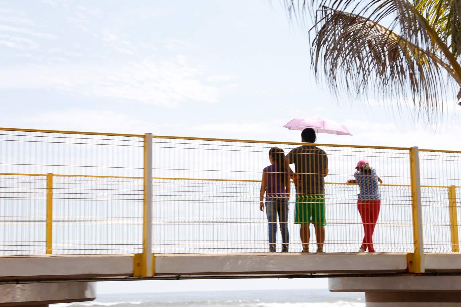 A man and two girls make a stop on a pedestrian bridge overlooking the beach. Shielded from the sun by a pink parasol, they look at the calm ocean underneath a clear blue sky.
