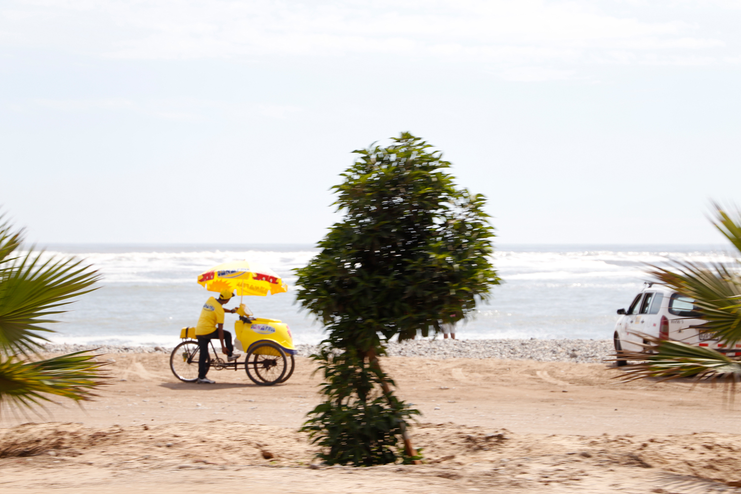 A man selling D'Onofrio brand ice cream on the beach is standing next to his shining yellow bicycle with a cooler box attached to the front and a large parasol spanning the entire vehicle.