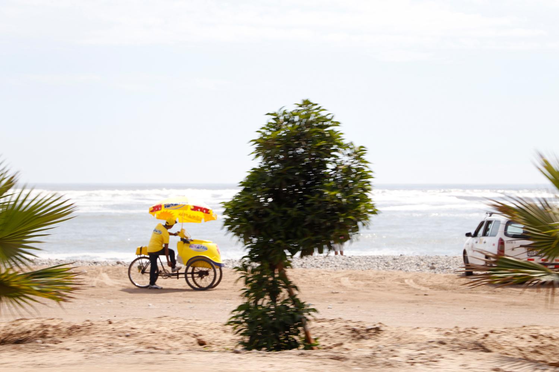 Ein Mann, der Eis der Marke D'Onofrio verkauft, steht neben seinem leuchtend gelben Fahrrad am Strand. Am Lenker ist eine Kühltruhe angebracht und ein großer Sonnenschirm überspannt das gesamte Gefährt.