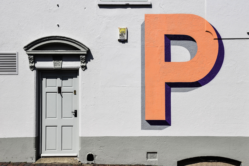 The uppercase letter P in a bright orange colour is painted on a white wall next to an ornate white door.