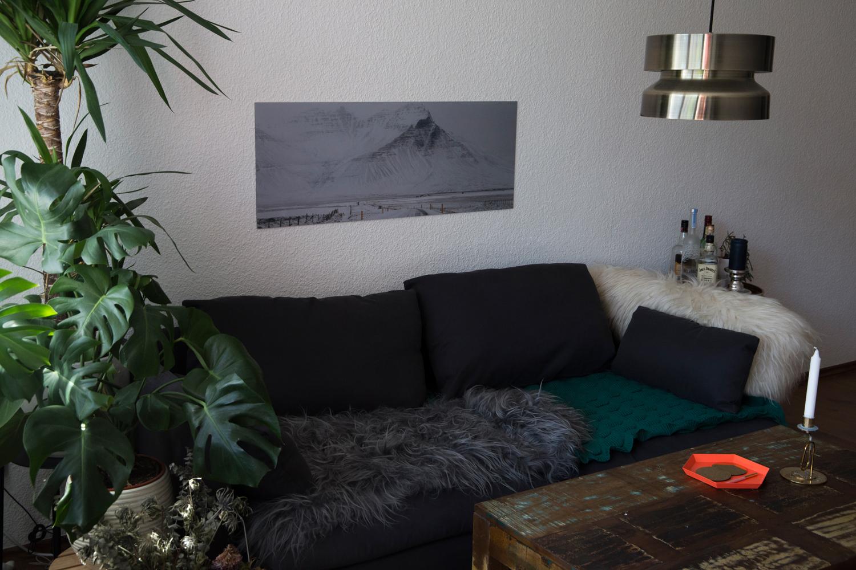 Das Foto einer verschneiten Berglandschaft in Island hängt als Alu-Poster-Druck in einem minimalistisch eingerichteten Wohnzimmer über einer Couch, neben der sich mehrere große Pflanzentöpfe und ein Abstelltisch mit Spirituosen befinden.