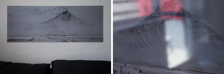 Links: Das Poster hängt an einer weißen Wand über einem dunkelblauen Sofa. Rechts: Bei direkter Lichteinstrahlung sind auf der Aluminiumoberfläche verschwommene Spiegelungen zu erkennen.