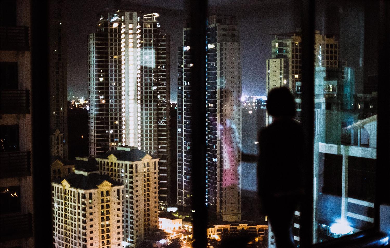 Die Silhouette einer Person zeichnet sich vor einer breiten Glasfront ab, die den nächtlichen Blick auf eine Reihe von Hochhäusern in Manila freigibt.