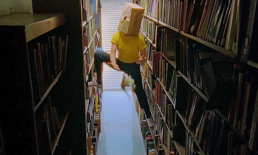 Im Musikvideo zu 'Heart Attack' von Tune-Yards hat sich eine Person mit Papiertüte über dem Kopf auf die Regalbretter in einer Bibliothek gestellt und lässt erschrocken ein Buch zu Boden fallen.