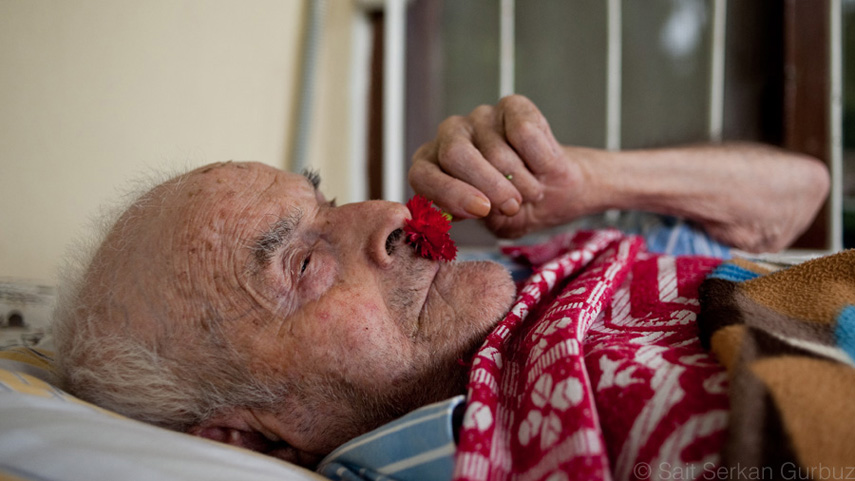 An old Armenian man is lying on the bed and holding a shining red carnation to his nose.